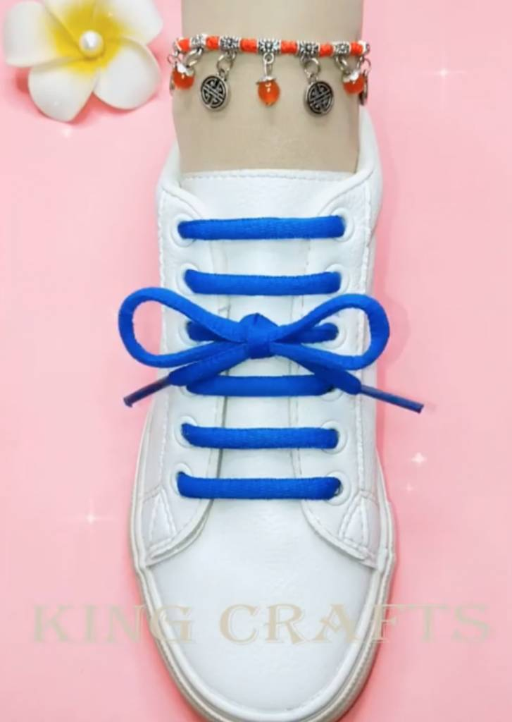White shoes with blue shoe lace in a straight line pattern